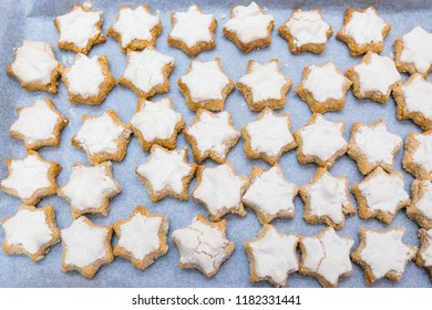 Looking down on flat lay of home baked imperfect star shaped cinnamon Swiss or German style Christmas cookies - known as Zimtsterne
