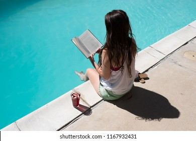 Looking down on girl reading a novel by the pool in shorts and tan top with a red punch and sandals at her side. Reading a book by an outdoor pool in the sun.