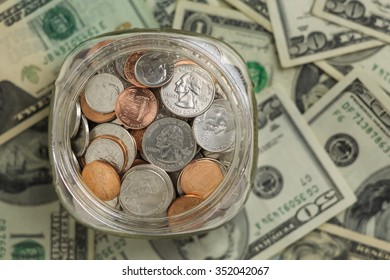 Looking down on glass jar filled with coins on a background of paper money. Small savings add up.