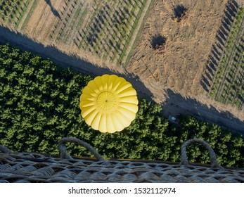Looking down on hot air ballon and farm crops below