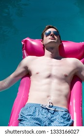 Looking down on hot sexy white man with defined abs lounging in a swimming pool on a pink raft in the sun wearing aviator sunglasses relaxing. Fit Caucasian man  on a raft in an outdoor swimming pool.