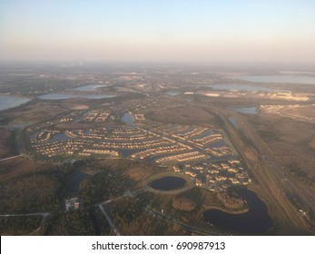 Looking down on Orlando, Florida from an airplane. Orlando suburbs. Poor air quality and smog hang around the horizon. Swampy landscape of the south.