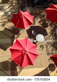 Looking down on red umbrellas, table and chairs with no people