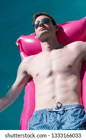 Looking down on sexy white man lounging in a swimming pool on a pink raft in the sun wearing aviator sunglasses relaxing. Fit Caucasian man floating on a raft in an outdoor swimming pool in the summer