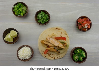Looking Down on Single Fajita and Toppings on wooden background