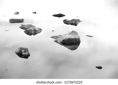 Looking down on some stepping stones in monochrome in a pond in Norway