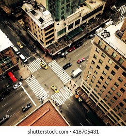 Looking down on to the streets of New York City with New York yellow taxis and people crossing the street going to work. Instagram style image.