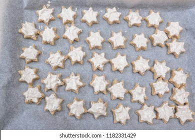 Looking down on tray of ready to bake cinnamon star Christmas cookies with glazing on baking paper - uncooked, messy and untidy