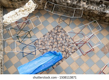 Looking down on white wire linen drying racks over a blue and beige tiled patio in the open air. One airer has a blue cloth, another a white sheet, five are empty. Laundry day seen from above.