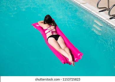 Looking down on woman laying on her stomach on a raft in a swimming pool wearing a bikini. White woman enjoying the sun in an outdoor swimming pool lounging on a pink raft. Top view.