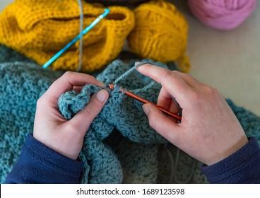 Looking down on Woman's hands Crocheting blue yarn