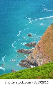Looking down over cliffs to a rocky foreshore and the deep blue ocean