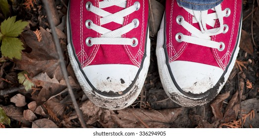 Looking down at a pair of dirty converse shoes in the leaves and mud