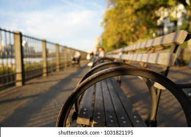 Looking down the Promenade lined with old wooden benches looking out to the New York skyline during sunset. Location: Brooklyn Heights Promenade