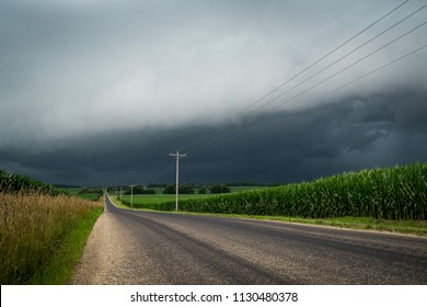 Looking down a rural midwest country lane with cornfields either side as a dangerous storm approaches.