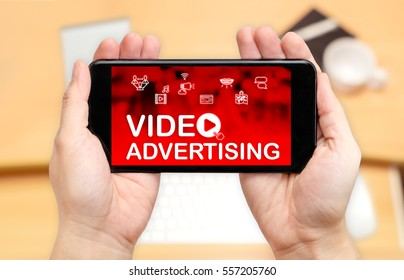 Looking down to see two hand holding mobile phone with Video advertising word on screen and blur desk office background,Digital content concept