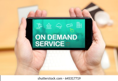 Looking down to see two hand holding mobile phone with On demand service word on screen and blur desk office background,Online shopping concept