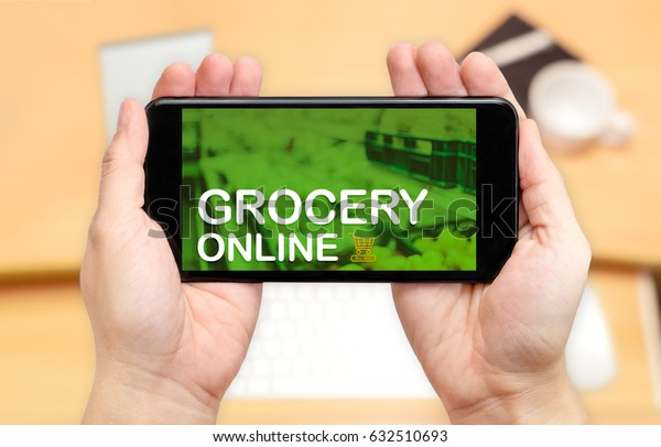 Looking down to see two hand holding mobile phone with Grocery online word on screen and blur desk office background,Online shopping concept