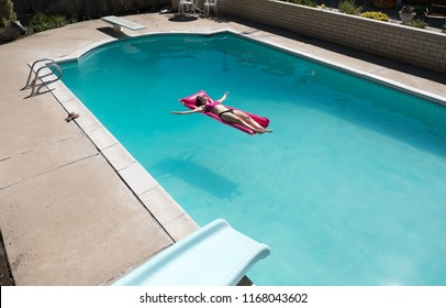 Looking down at sexy woman in bikini floating on a raft in an outdoor backyard swimming pool alone. Floating in a swimming pool on a raft view from slide above. Looking down on woman in swimming pool.