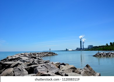 Looking down the shoreline of Lake Michigan with a powerplant in the distance.