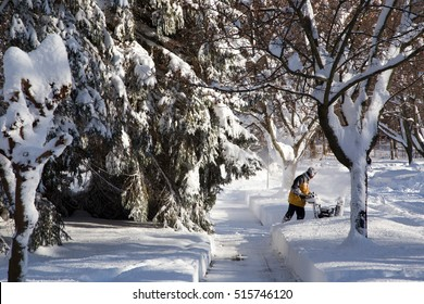 looking down the sidewalk at man with a snow blower clearing deep snow from his driveway