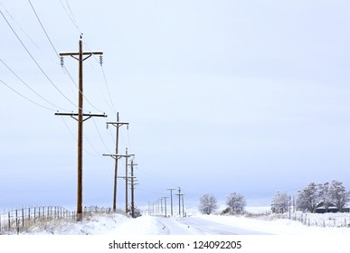 Looking down a snowy winter road with a line of telephone poles
