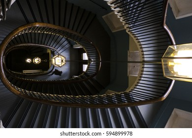 Looking down a spiral staircase at a chandelier hanging down.