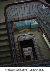 Looking down to stairwell with Spiral staircase with thick wooden railing and residents chest in old Russian Stalin era residential building in day light