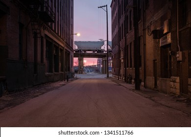 Looking down a street with vintage brick buildings at a freight train car at rest as the sun rises