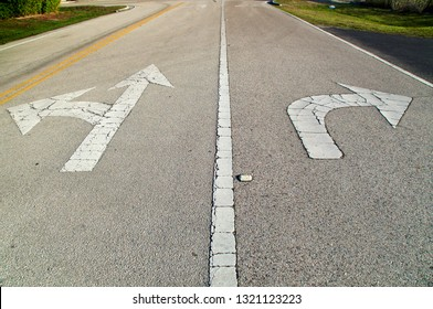 Looking down a stretch of empty road showing directional arrows painted on the road, pointing straight and left, and another pointing right, they are old and cracked.