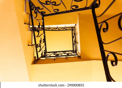 Looking down a three story staircase in ancient building
