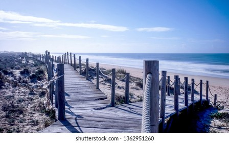 Looking down two wooden decking pathways forming a fork in the road, both heading down to a sweeping sandy beach with the blue sea and blue sky in front  Praia Da Lagoa, Algarve, Portugal.