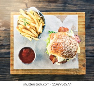 Looking down at an upmarket luxury burger with chips and a tomato salsa.