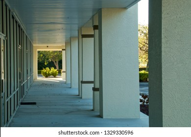 looking down walkway in front of generic florida strip mall with shop doors on the left and columns on the right.