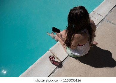 Looking down white Caucasian woman with long brunette hair sitting on the edge of a swimming pool with her feet in the water looking at a smartphone.  Looking at mobile phone by outdoor swimming pool.