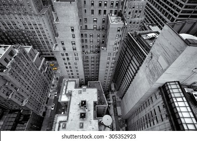 Looking down at yellow cabs in the streets of New York, USA, as small colorful dots in black and white composition of tall skycrapers