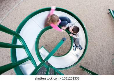 Looking down at a young boy and girl sliding down a spiral metal slide in a playground, motion blur, fisheye perspective