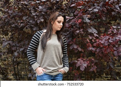 Looking downward - teen female with long dark hair - dark red background