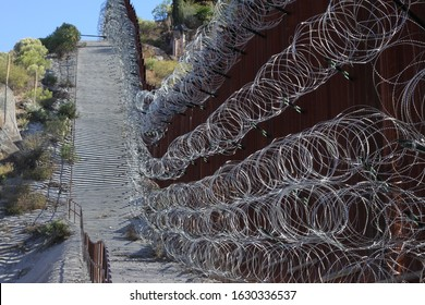 looking east at along bollard style border wall hung with barbed wire on the US-Mexico border 5158