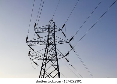 Looking up at electricity pylons, cables and fencing against a clear blue sky