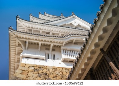 Looking up to the elegant architecture of the main tower of Himeji Castle with its white eaves and dark colored roof tiles.  Himeji is considered  the prototype of Japanese castle architecture.