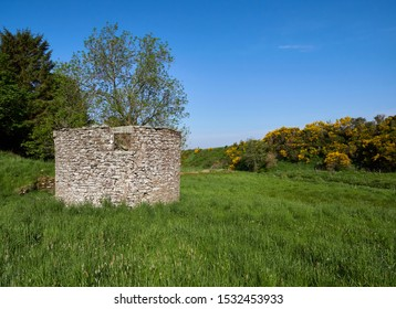 Looking end on at an old stone ruined building with a square window in a grass field in a small Valley near to Guthrie, Forfar, Angus in Scotland.