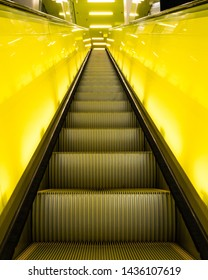 Looking Up an Escalator with Illuminated Yellow Glass