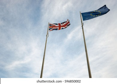 Looking up at EU and UK flags blowing in the wind
