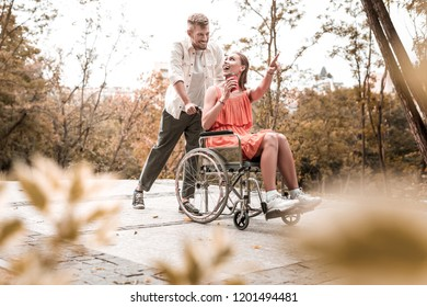 Looking excited. Cheerful emotional disabled girl sitting in the wheelchair and pointing to the distance while showing beautiful view to her smiling boyfriend