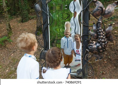 Looking at a false glass. Children enjoying with reflections in a distorted mirror