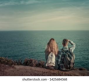 looking the far sea couple sitting on adventure coast