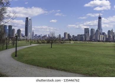 Looking faraway, the left side is Jersey City and the right side is New York City. The front ground is a small road in a green park./Jersey City and New York  in Spring Season