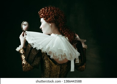 Looking for a flaw. Medieval redhead young woman in golden vintage clothing as a duchess looking in the mirror on dark green background. Concept of comparison of eras, modernity and renaissance.