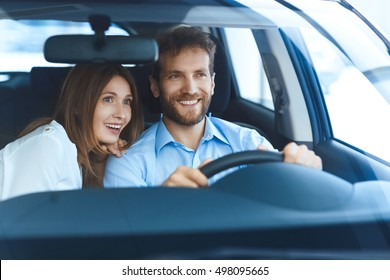 Looking forward to travel together. Happy mature couple sitting in their brand new car smiling joyfully